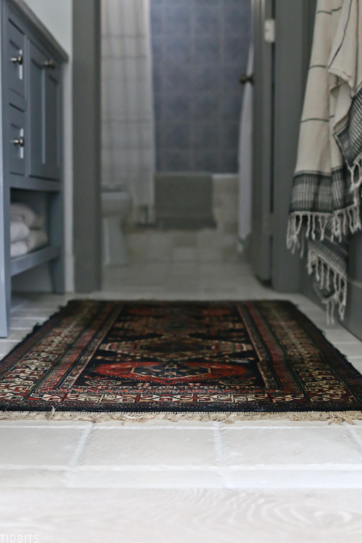 antique rug placed on floor in split bathroom