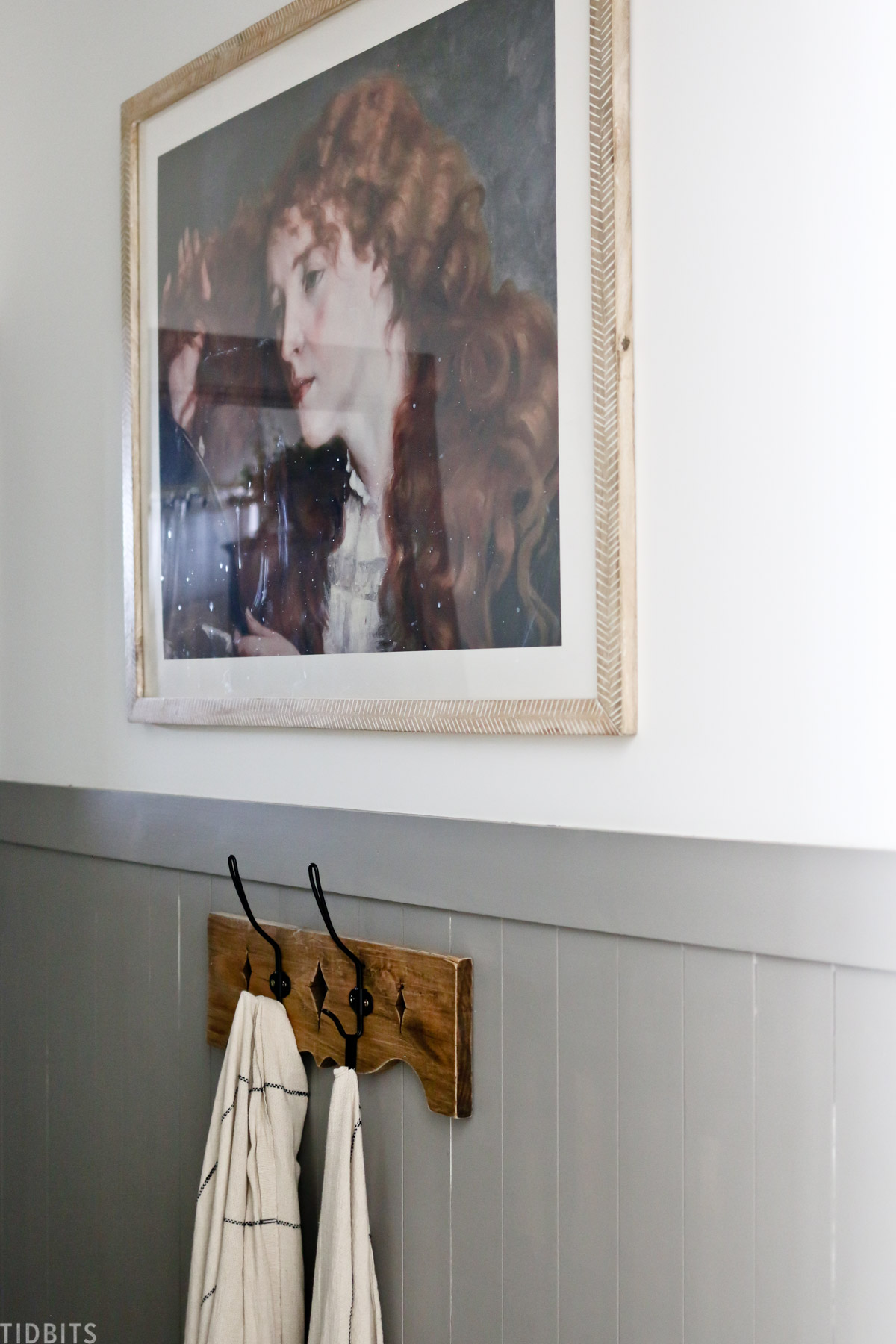 antique artwork hanging in bathroom above towel hooks