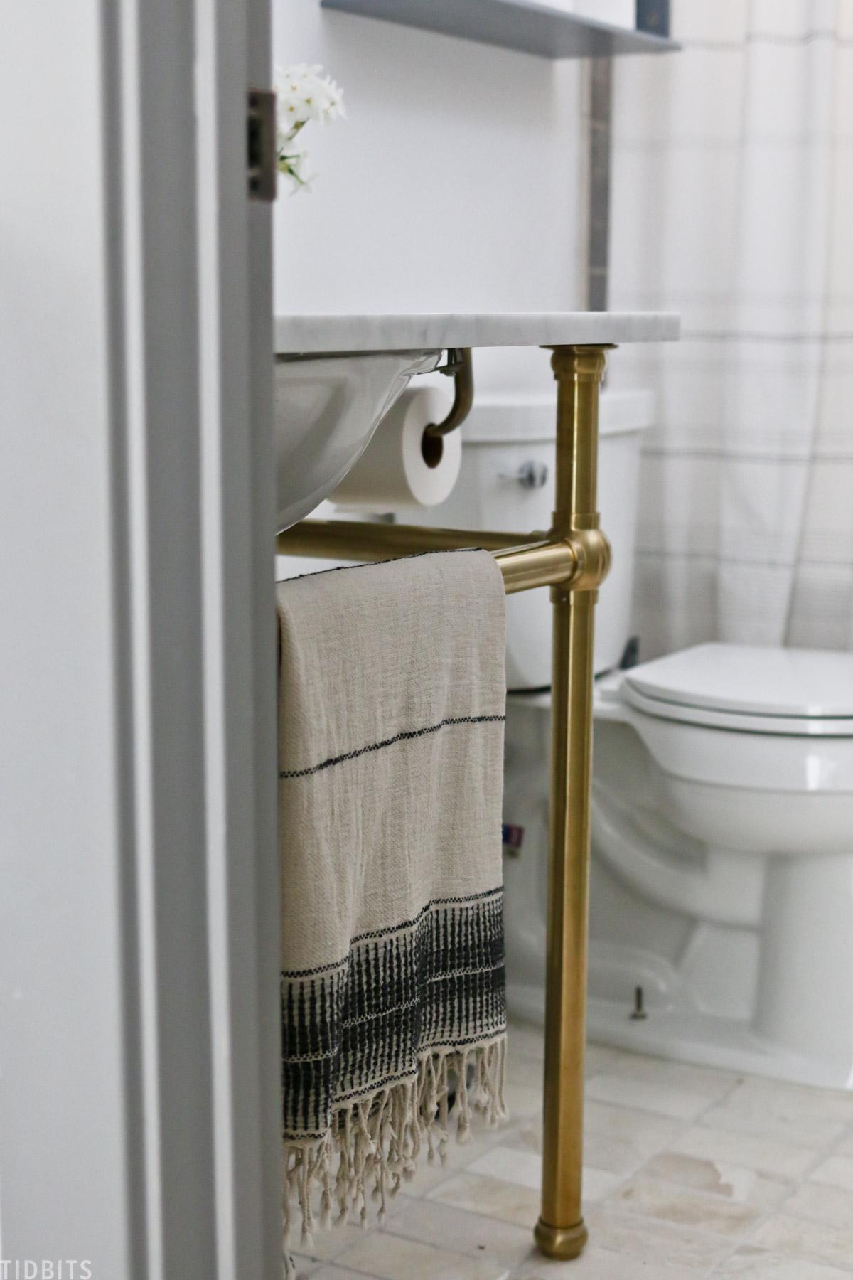 towel hung underneath exposed bathroom sink next to toilet