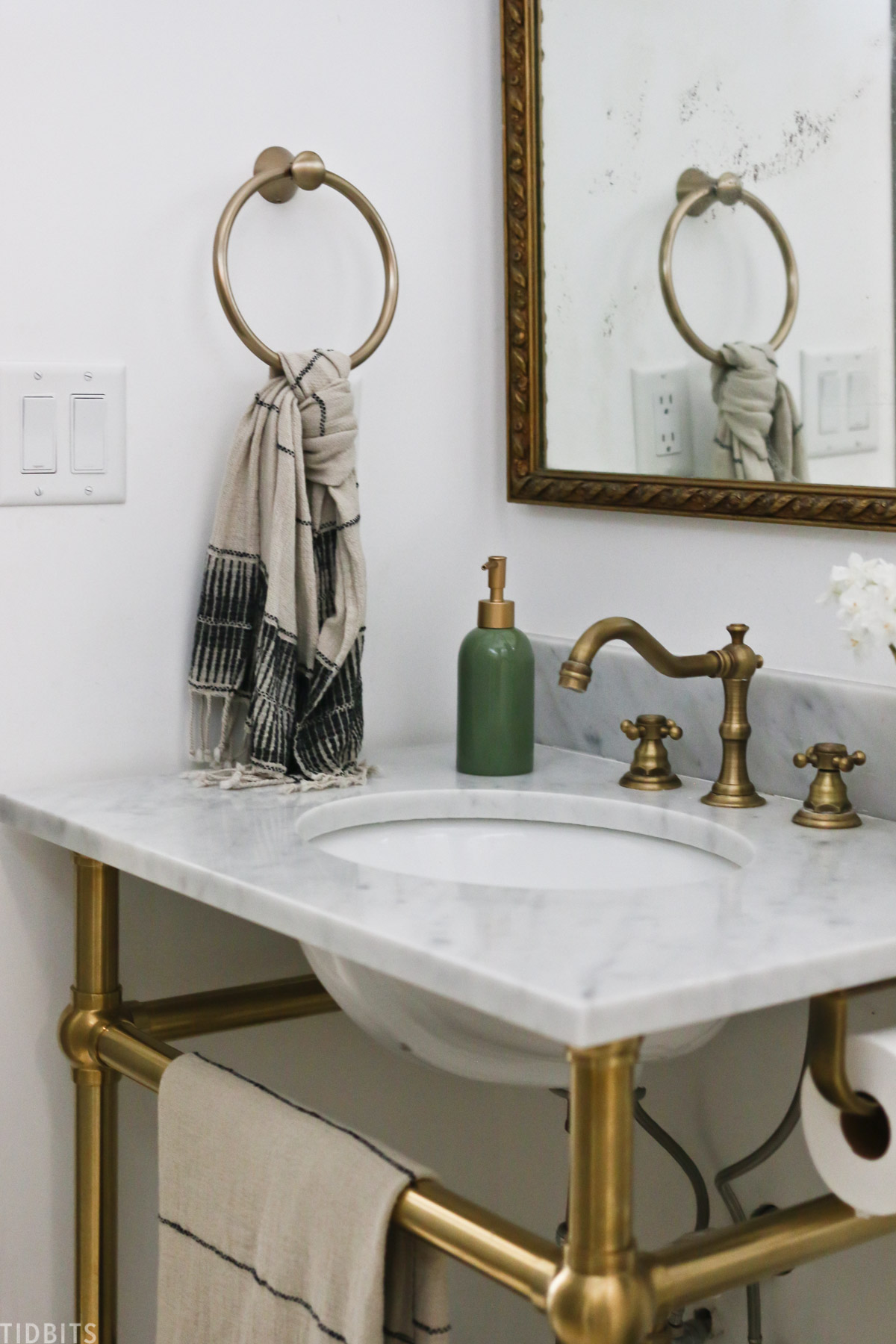 bathroom sink with gold colored finishes and green colored soap dispenser