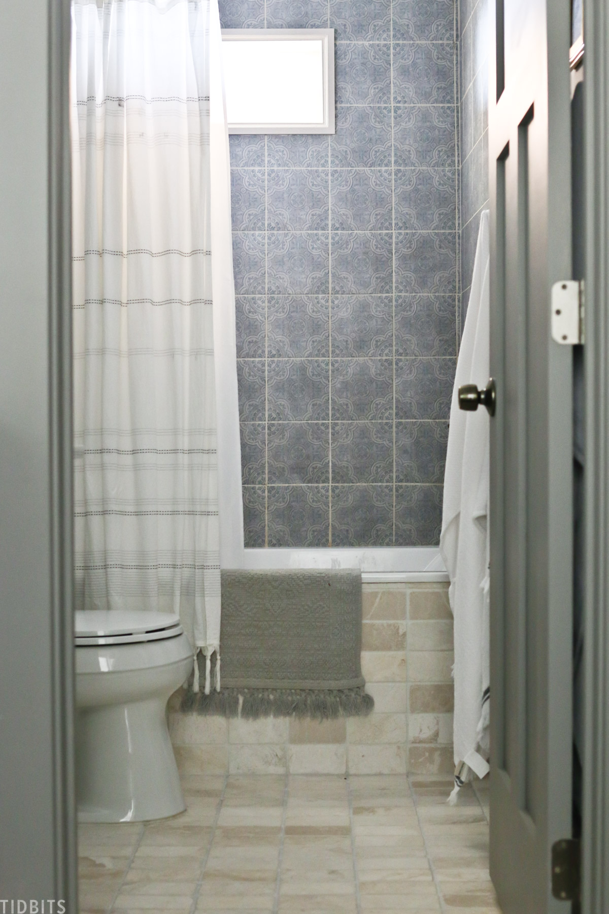 blue tiles installed above bathtub and neutral colored tiles installed on the floor of a bathroom