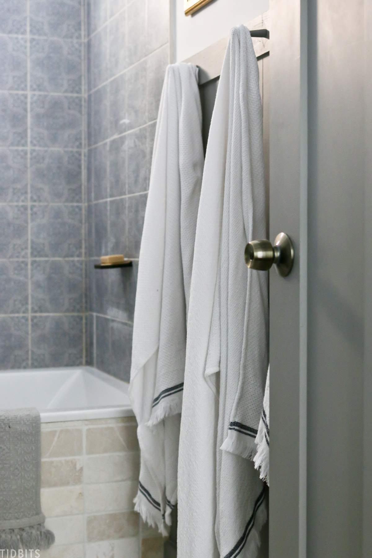 two towels hanging on towel rack next to bathtub