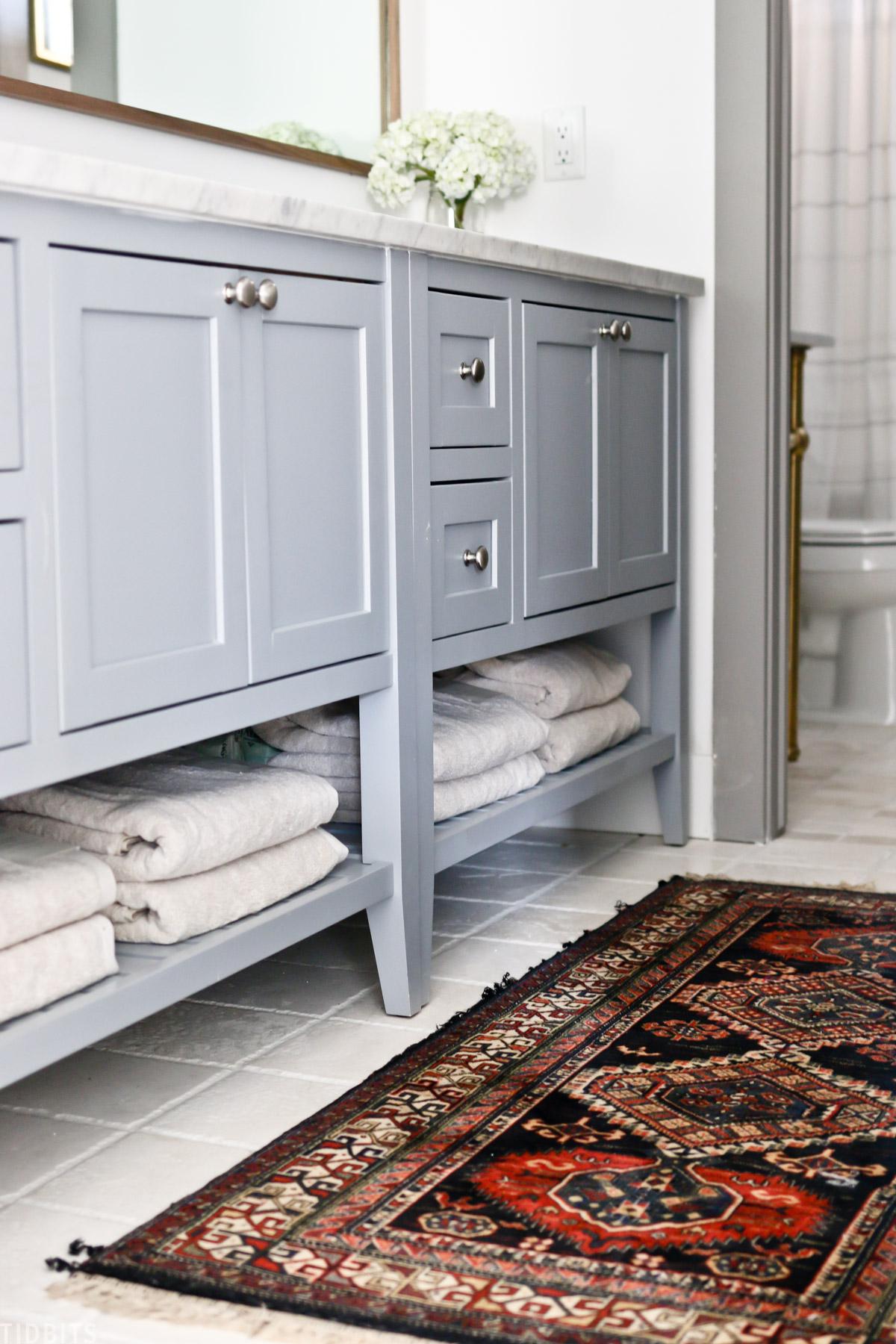 split bathroom vanity with towels stored underneath bathroom sink cabinets