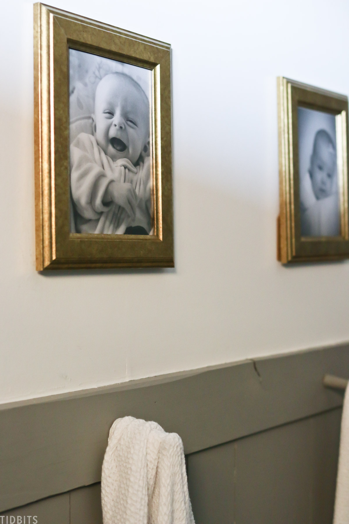 baby pictures hanging on the wall in split bathroom