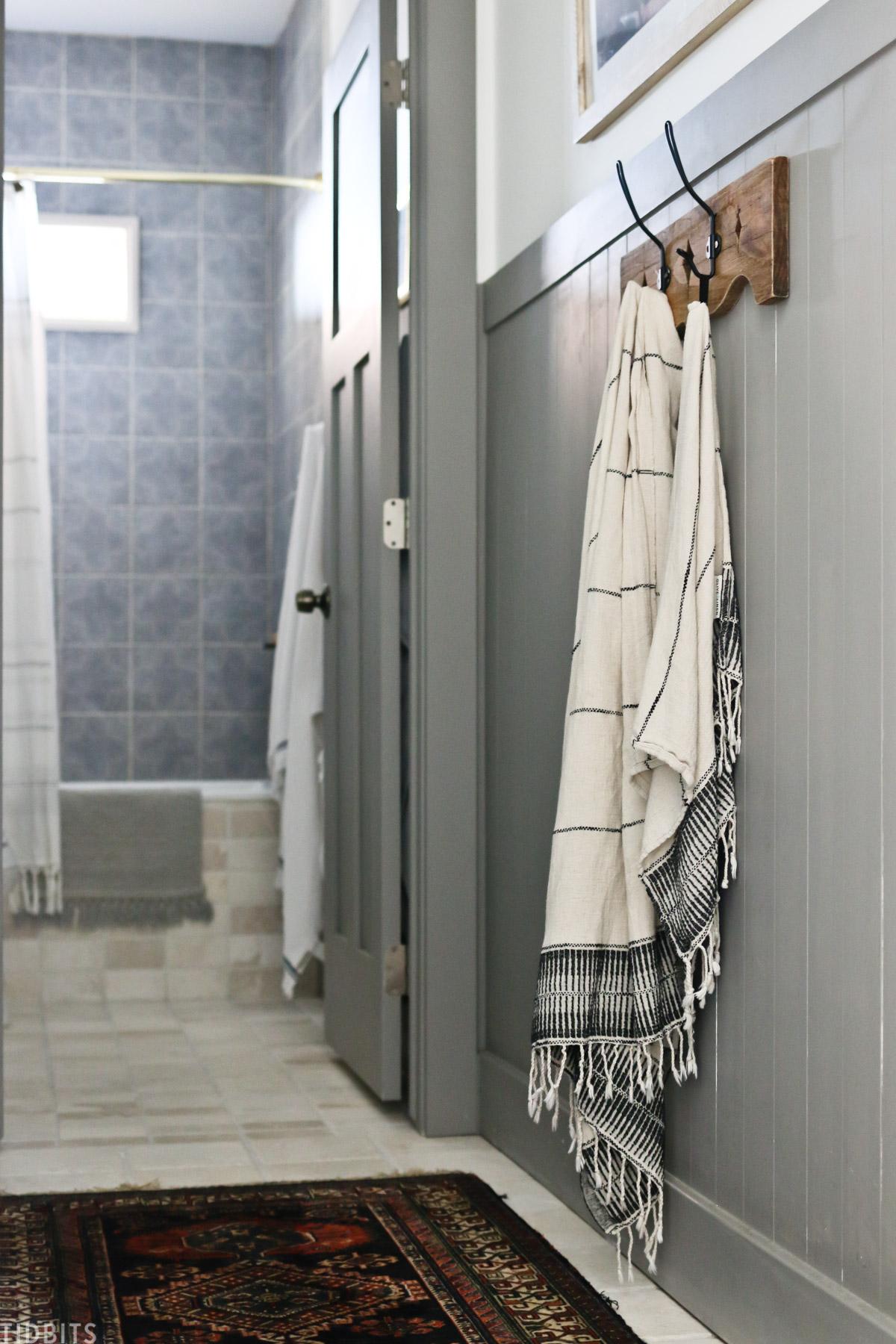 wooden towel rack with metal hooks hanging in split bathroom