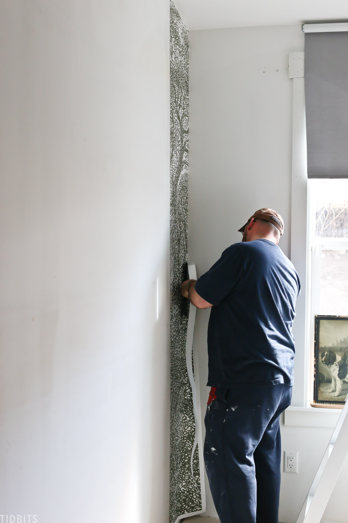 man installing one part of the wallpaper mural in a kids' bedroom