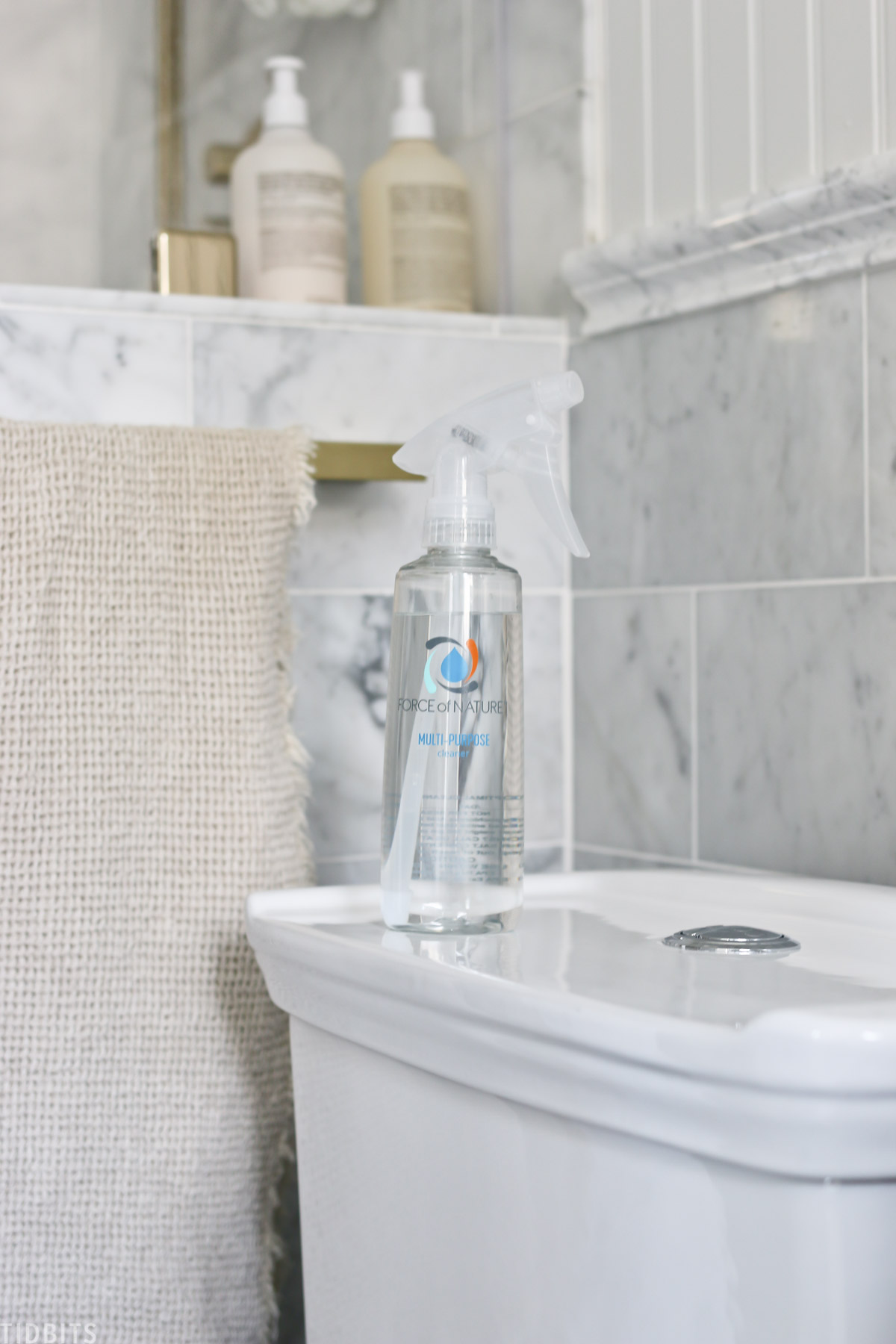 Force of Nature spray bottle that's filled with disinfectant spray and placed on top of a toilet