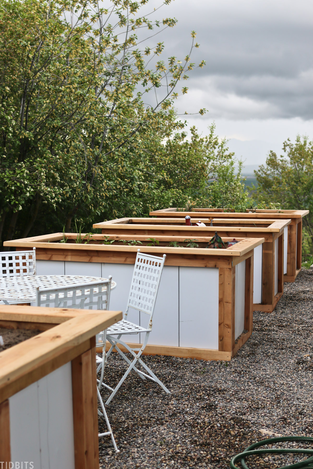 outdoor table and chairs in between tall raised garden beds