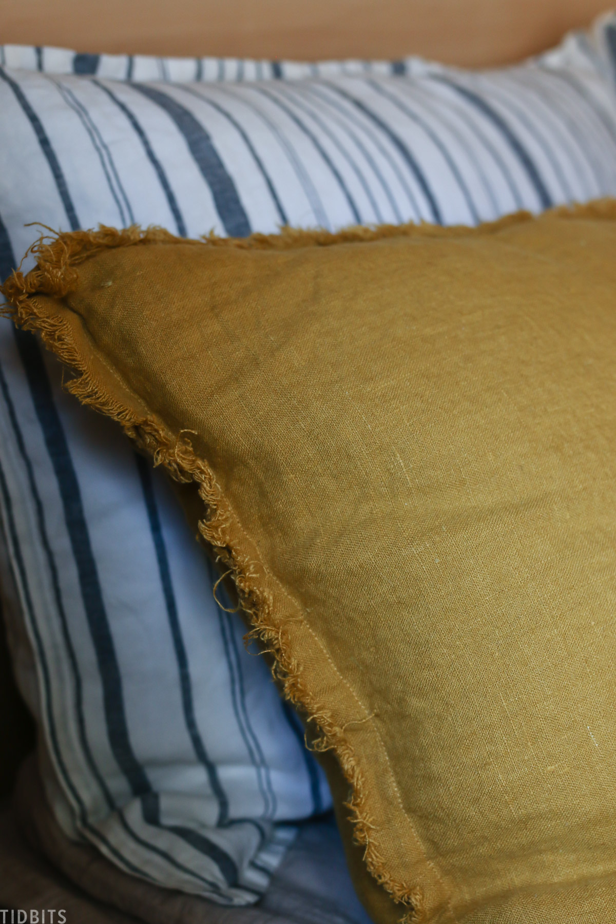 yellow sham with loose threading on the sides of the pillow