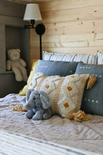 layered kids bed with throw pillows and stuffed elephant