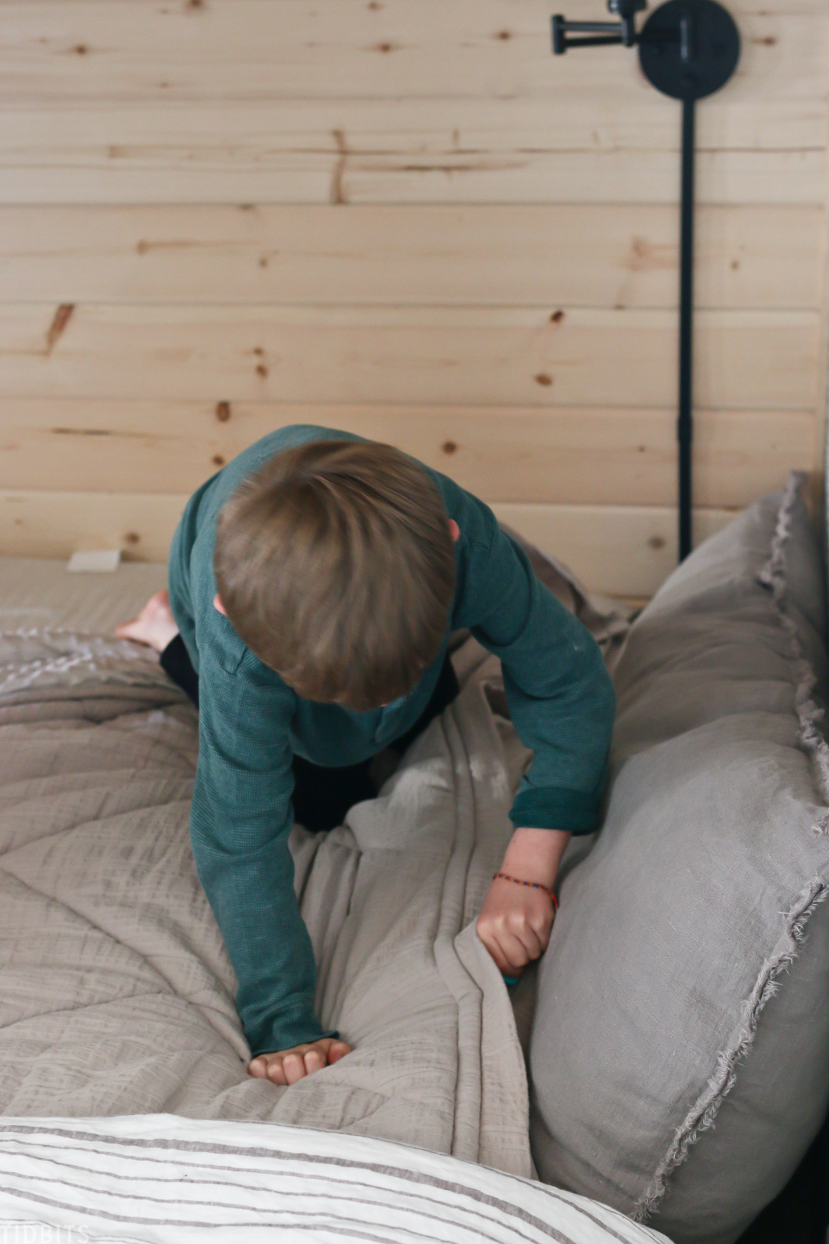 young boy making his bed