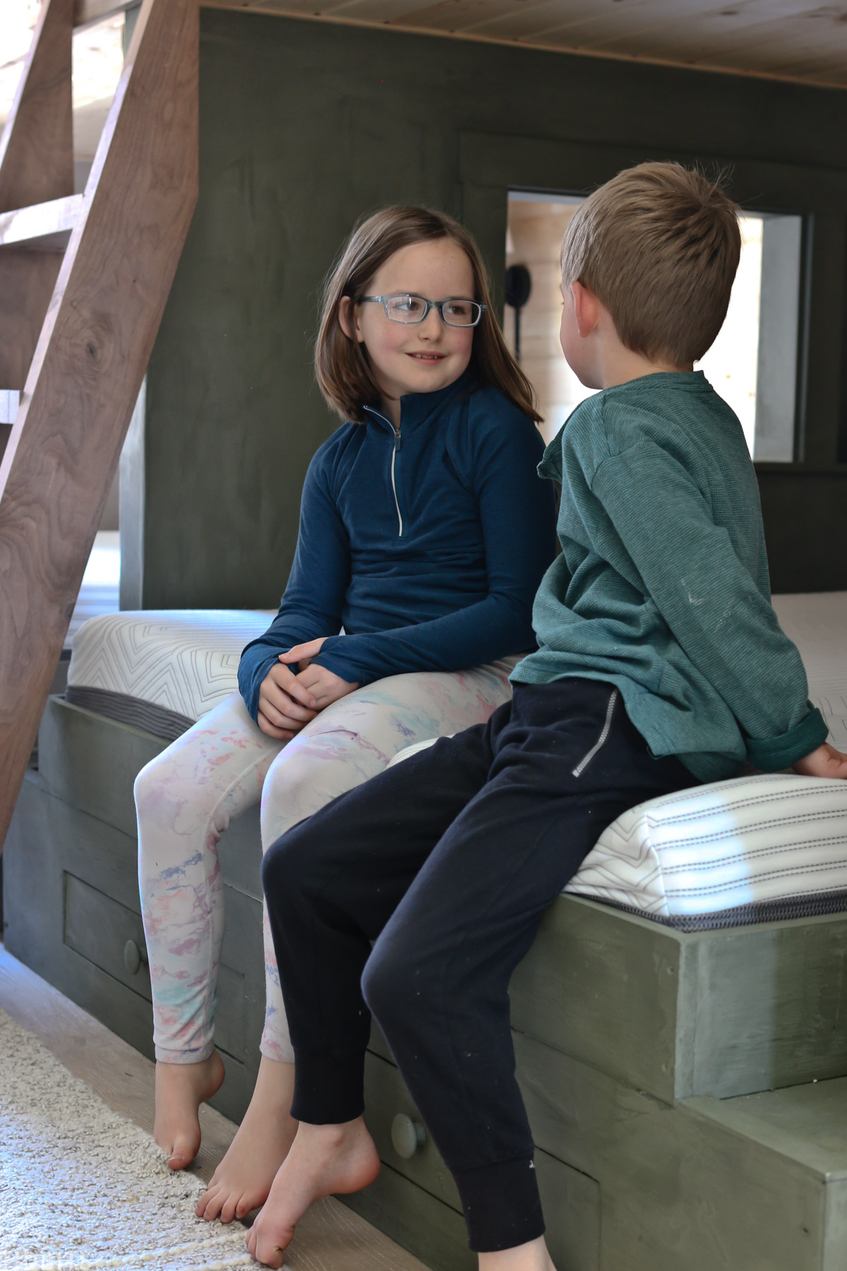 two children sitting on a kids platform bed with a memory foam mattress made by Mattress Firm