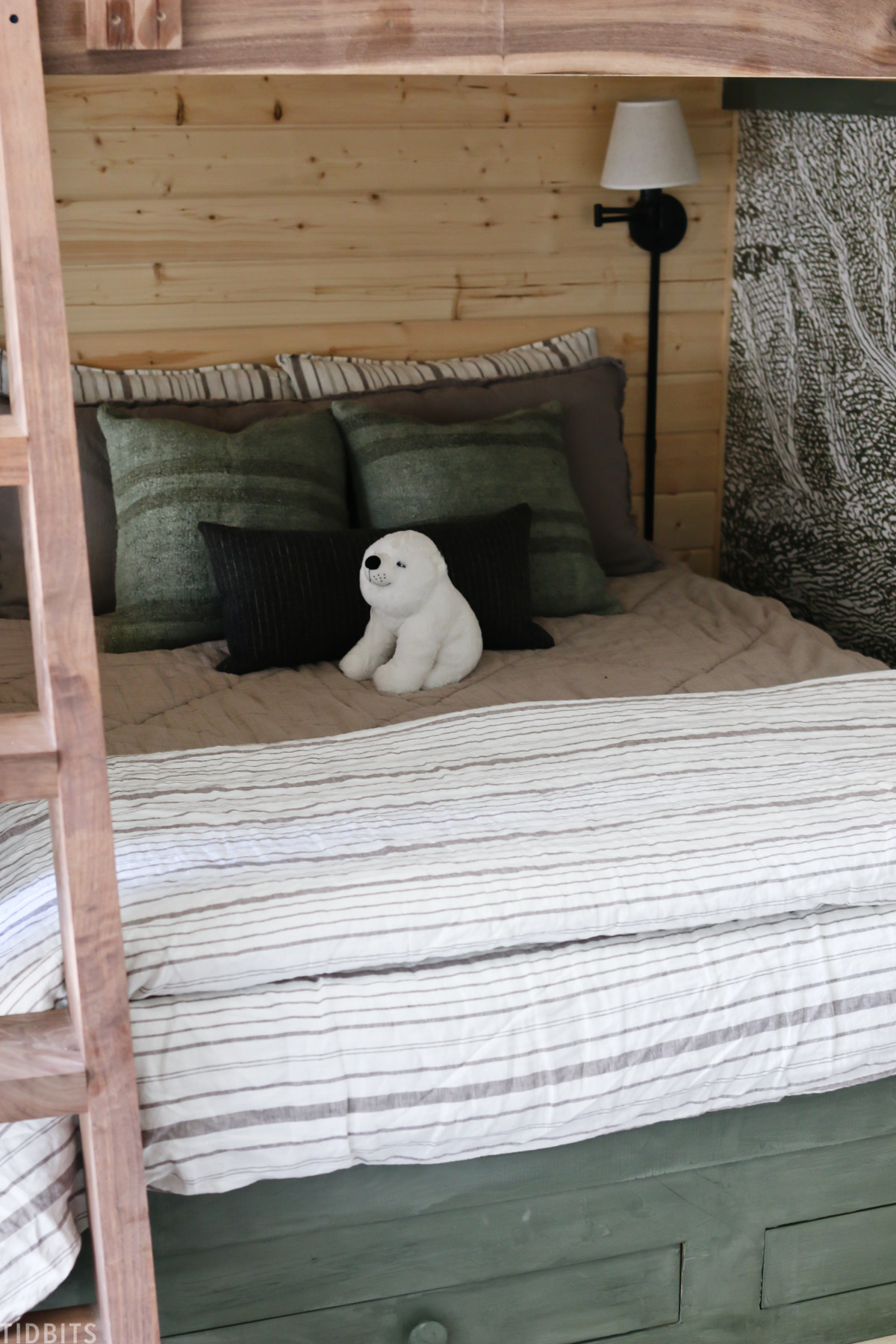kids bed layered with linens, throw pillows, and a stuffed polar bear