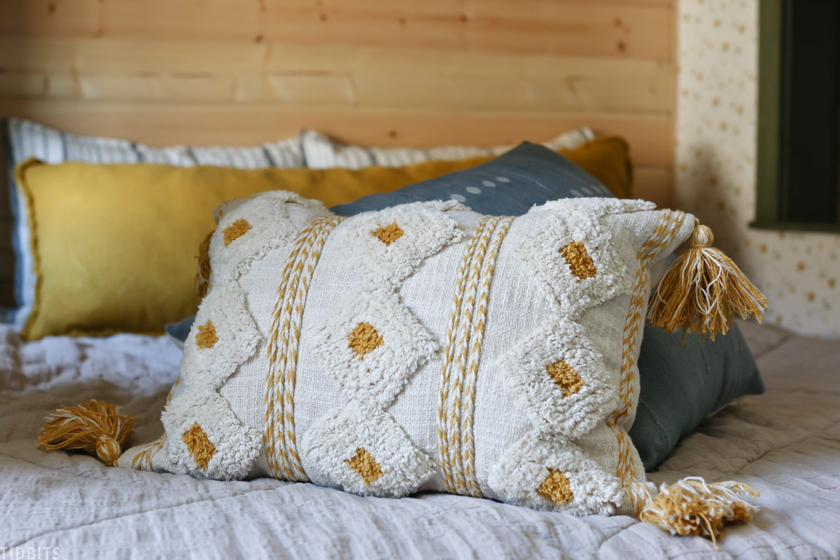 Bohemian yellow tassel pillow placed on kids bed with other throw pillows