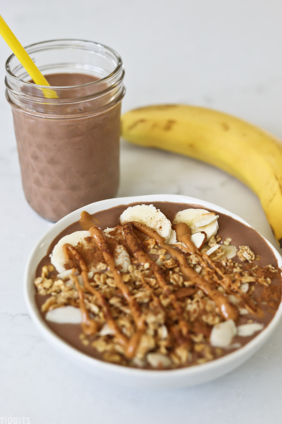 chocolate peanut butter smoothie bowl placed next to a banana and a mason jar filled with a smoothie containing similar ingredients