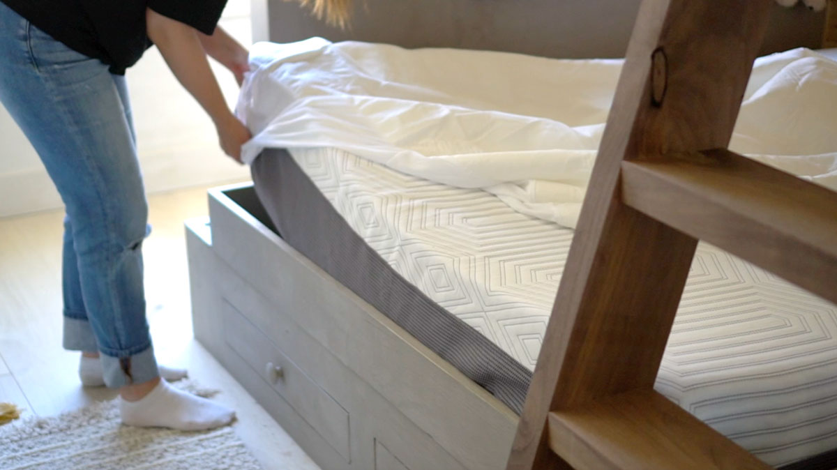 putting on a mattress protector on kids bed