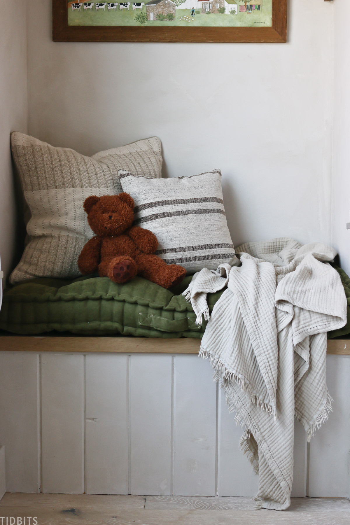 teddy bear, throw pillows, a throw blanket, and a cushion on top of a built in bench