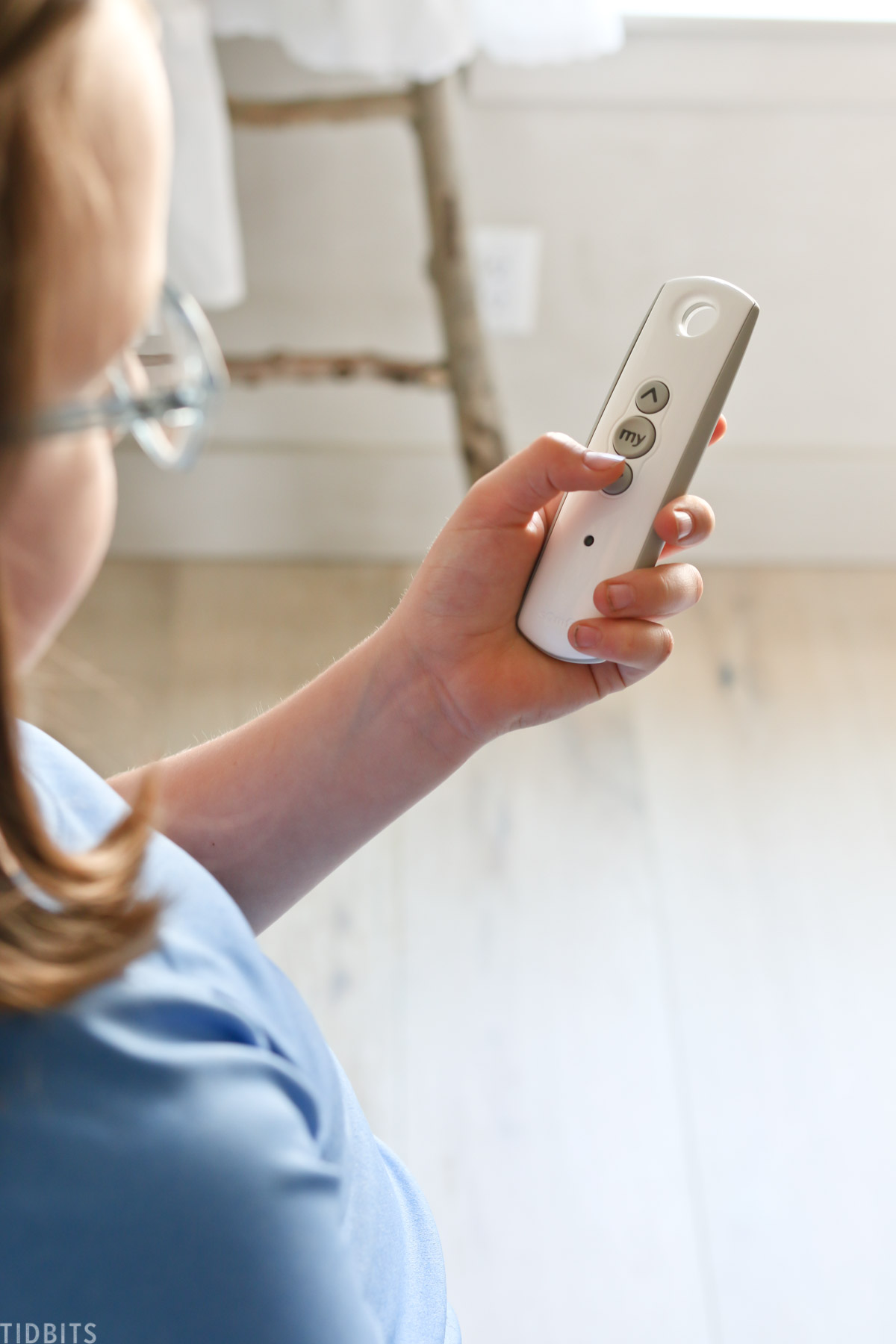 child holding remote control that operates a window treatment