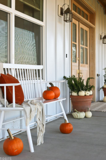 front porch decorated for fall with white and orange pumpkins plus a bench with pillow and blanket