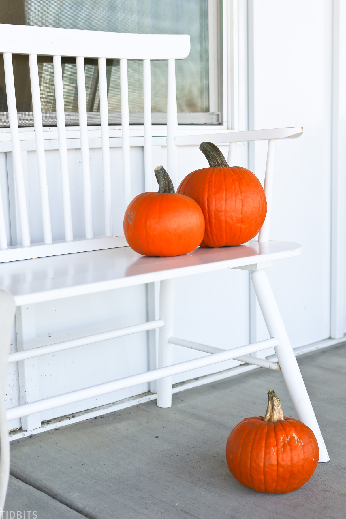three orange pumpkins placed on a bench on a front porch